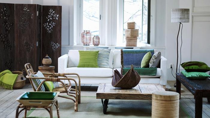 Deko in Grüntönen für Sitzgruppe in grossem Altbauwohnraum mit rustikalen Holztisch und Paravent im Hintergrund
